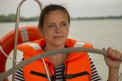 Leuke jonge vrouwenkapitein in het reddingsvest bij het roer van het jacht Stock Afbeeldingen