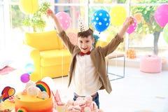 Leuke jongen dichtbij lijst met traktaties bij verjaardagspartij binnen stock foto's