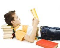 Leuke jongen die een boek op de vloer leest royalty-vrije stock afbeelding