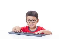 Leuke Jongen die een toetsenbord gebruiken Stock Foto's