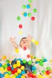 Leuke jongen die kleurrijke ballen speelt Stock Foto's