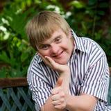 Leuke jongen die met benedensyndroom duimen omhoog in tuin doen Stock Foto