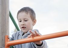 Leuke jongen die op kinderenspeelplaats in openlucht beklimmen Pre-school kind die pret op speelplaats hebben Jong geitje het spe stock afbeelding