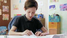 Leuke jongen die origami in zijn ruimte vouwen stock videobeelden