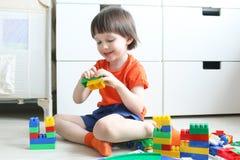 Leuke jongen die plastic blokken thuis spelen Stock Foto's