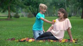 Leuke jongen die wildflowers aan moeder, prettige verrassing van gehouden van voorstellen stock footage