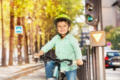 Leuke jongen die zijn fiets berijden op groen signaal van lichten stock fotografie