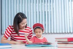 Leuke jongen die zijn schoolthuiswerk met zijn moeder doen, thuis, hij Stock Fotografie