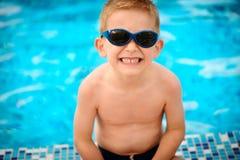 Leuke jongen die in zonnebril bij pool zitten Stock Foto's