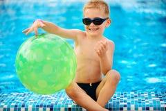 Leuke jongen die in zonnebril bij pool zitten Stock Fotografie