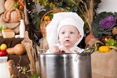 Leuke jongen in een kokpan Stock Afbeeldingen