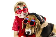 Leuke jongen en grappige brakhond in feestelijke zonnebril stock afbeelding