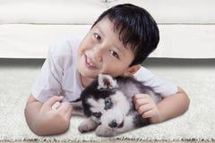 Leuke jongen en schor puppy thuis Royalty-vrije Stock Foto