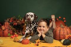 Leuke jongen en zijn hond in de decoratie van Halloween Royalty-vrije Stock Afbeeldingen