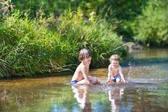 Leuke jongen en zijn kleine babyzuster in het water in meer royalty-vrije stock fotografie