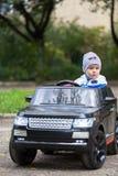 Leuke jongen in het berijden van een zwarte elektrische auto in het park stock afbeeldingen