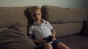 Leuke jongen het spelen videospelletjes thuis Hoge Resolutie stock videobeelden