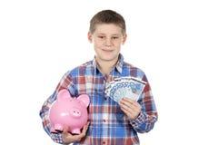 Leuke jongen met spaarvarken en bankbiljet Stock Afbeeldingen