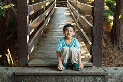 Leuke jongen op een brug Stock Fotografie