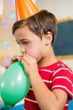 Leuke jongens blazende ballon tijdens verjaardagspartij Stock Afbeelding