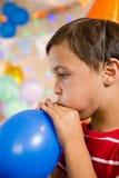 Leuke jongens blazende ballon tijdens verjaardagspartij Stock Fotografie