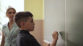 Leuke jongenstribune op de klaslokaalachtergrond van bord Onderwijs De Meisjes van Exellent en luie jongen stock video