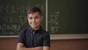 Leuke jongenstribune op de klaslokaalachtergrond van bord Onderwijs De Meisjes van Exellent en luie jongen stock videobeelden