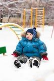 Leuke jongenszitting in sneeuw openlucht Royalty-vrije Stock Afbeeldingen