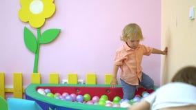 Leuke Kaukasisch weinig jongen en babymeisje die en in multi gekleurde balpool lachen spelen peuter stock videobeelden