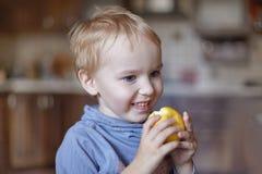 Leuke Kaukasisch weinig jongen met blauw ogen en blondehaar eet gele appel, houdend het op de handen, het glimlachen stock fotografie
