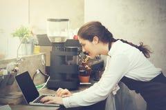 Leuke Kaukasische bezig het werken met laptop aan de teller van de koffiewinkel stock foto's