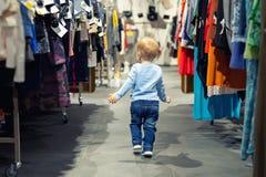 Leuke Kaukasische blonde peuterjongen die alleen bij klerendetailhandel tussen rek met hangers loopt De baby ontdekt het volwasse stock afbeeldingen