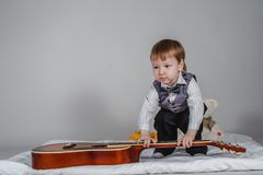 Leuke Kaukasische jongen in vlinderdas en vest met gitaar op grijze achtergrond stock fotografie