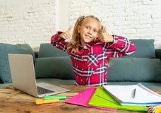 Leuke Kaukasische vrolijke elementaire student die gelukkig terwijl het doen van thuiswerk en thuis binnen het bestuderen op haar royalty-vrije stock fotografie