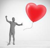 Leuke kerel in het kostuum die van het morpsuitlichaam een ballon gevormd hart bekijken stock afbeeldingen