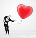 Leuke kerel in het kostuum die van het morpsuitlichaam een ballon gevormd hart bekijken stock foto