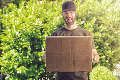 Leuke kerel met een gelukkige grijns die een levering maken stock foto's