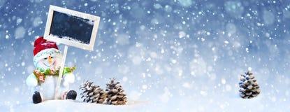 Leuke Kerstmissneeuwman met Denneappel op de Sneeuw Stock Afbeeldingen