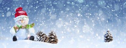 Leuke Kerstmissneeuwman met Denneappel op de Sneeuw Royalty-vrije Stock Afbeelding