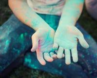 Leuke kind` s handen vuil wegens kleurrijk poeder stock afbeeldingen