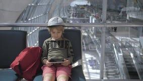Leuke kind speelspelen, het letten op film op smartphone in luchthaven stock videobeelden
