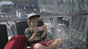 Leuke kind videopraatjes op smartphone in luchthaven vóór vertrek stock videobeelden