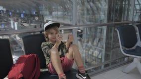 Leuke kind videopraatjes op smartphone in luchthaven vóór vertrek stock video