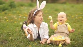 Leuke kinderen in de weide met een Pasen-mand Pasen-concept, lichtgroene, gele kleuren stock video