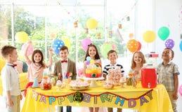 Leuke kinderen dichtbij lijst met traktaties bij verjaardagspartij binnen stock afbeelding