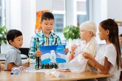 Leuke kinderen die ecologische problemen bespreken op school stock foto's