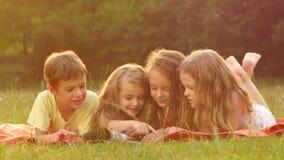 Leuke kinderen die een boek in de tuin samen zomer een lezen goede dag Sluit omhoog stock videobeelden