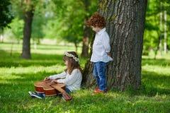 Leuke kinderen die gitaar spelen Stock Afbeelding
