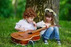 Leuke kinderen die gitaar spelen Stock Afbeeldingen