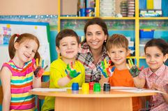 Leuke kinderen die met leraar bij peuterklasse trekken Stock Foto's